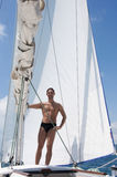 Sexy young man sailing on white yacht Royalty Free Stock Photography