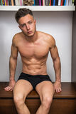 Sexy young man sitting shirtless in his room Royalty Free Stock Photo
