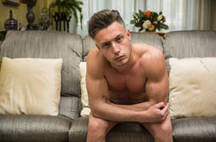 Sexy young man sitting shirtless in living-room. Sexy handsome young man sitting shirtless in his living-room on a couch, looking at camera Stock Photo