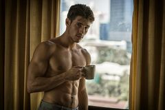 Sexy young man standing shirtless by curtains with coffee royalty free stock photo