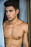 Sexy young man standing shirtless by curtains. Sexy handsome young man standing shirtless in his bedroom next to window curtains Royalty Free Stock Photos