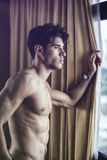 Sexy young man standing shirtless by curtains. Sexy handsome young man standing shirtless in his bedroom next to window curtains Stock Photo