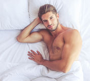 Young man. Top view of muscular young man looking at camera with sensual smile while lying in bed