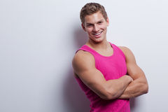 young man wearing undershirt and jeans, posing at white wal Stock Images
