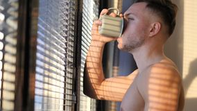 young man by window with coffee cup