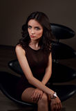 Sexy young model in brown dress sitting on the black chair on da Royalty Free Stock Photo