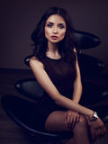Sexy young model in brown dress sitting on the black chair on da Stock Photography