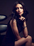 Sexy young model in brown dress sitting on the black chair and p. Osing on dark shadow background in fashion watch on the hand Stock Images