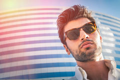 Sexy young modern man. Sunglasses, city building. Hairstyle Royalty Free Stock Image