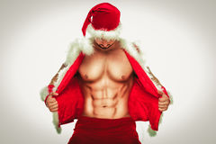 Sexy. Young muscular man wearing Santa hat demonstrate his Royalty Free Stock Photos