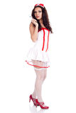 Sexy young nurse holding a syringe. Sexy young nurse with long curly hair wearing red high heels shoes and holding a syringe  on isolated white background. High Royalty Free Stock Photo