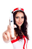 Sexy young nurse holding a syringe. Selective focus image of a sexy young nurse  holding a syringe and looking at camera smiling on isolated white background Royalty Free Stock Photos