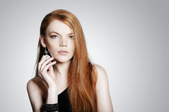 Young red hair woman. With jewellery on grey background stock image