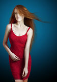 Young red hair woman in a red dress. Young red hair woman in red dress on dark blue background stock photography