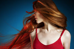 Young red hair woman. In red dress on dark blue background royalty free stock photo