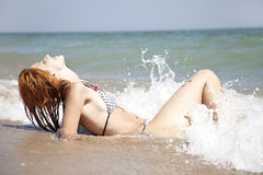 Sexy young red-haired girl on the beach. Stock Photos