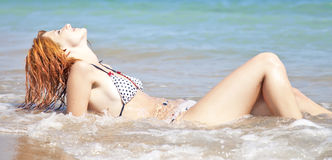Sexy young red-haired girl on the beach. Outdoor photo Royalty Free Stock Images