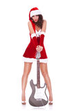 Young santa woman with guitar. Young santa woman with great legs holding her electric guitar on the floor, over white background stock photos