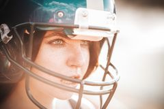 Sexy young sportive girl in uniform of rugby football player in action on the stadium. American football woman player stay on royalty free stock photos