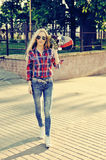 Sexy young stylish woman model girl in bright modern clothes and. Sunglasses. Walking with skateboard in the street Stock Image