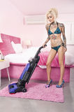 Sexy young tattooed woman in bikini vacuuming bedroom Royalty Free Stock Photos