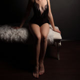 Sexy young unrecognizable woman in sensual black lingerie, sitting on white bench with fur, barefoot. Royalty Free Stock Photos