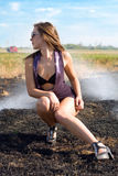 Young woman. Sitting in the burning field stock photography