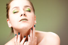 Sexy young woman. Portrait of sexy young woman with bare shoulders and green face makeup; studio background Royalty Free Stock Photo
