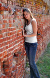 young woman against a brick wall Stock Photos