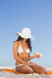 Sexy young woman applying sun cream while sitting on her towel Royalty Free Stock Photo