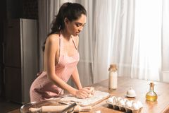 Young woman in apron preparing dough. At home royalty free stock images