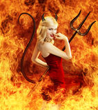 Sexy young woman as devil in fire Royalty Free Stock Image