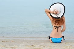 Sexy young woman in bikini and hat sitting on the beach, space f Stock Photo