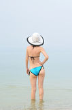Sexy young woman in bikini and hat standing in the sea, space fo Stock Images