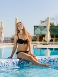 Sexy young woman in a bikini sitting on a pool background. Natural beauty concept. Copy space. Fantastic, sporty, sensual young woman in a black bikini sitting Royalty Free Stock Images