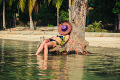 Sexy young woman in bikini by tree on tropical beach Royalty Free Stock Image