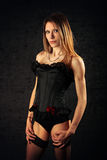 Sexy young woman in black basque and stockings. Sexy attractive young lady in lacy black underwear looking sultry Royalty Free Stock Photo