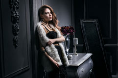 Sexy young woman in black dress and white fur jacket. Posing in vintage dark interior Stock Photo