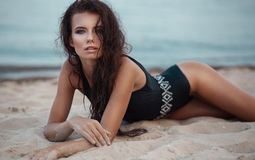 Sexy young woman in black fashion swimsuit on the beach looking. At camera Stock Photography