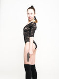 Sexy young woman in a black lace bodysuit with braided hair is holding a gun. on the feet thick black stockings Royalty Free Stock Photography