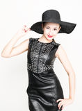 Sexy young woman in black leather dress with braided hair. a big black hat on his head Royalty Free Stock Image