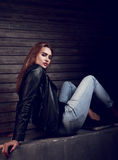 Sexy young woman in black leather jacket sitting on the stone an. D looking serious. Toned portrait Royalty Free Stock Photo