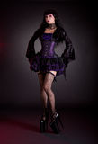 Young woman in black and purple costume. Wearing extra high heels royalty free stock photos