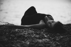 young woman in black skin-tight dress lying on the beach in water Royalty Free Stock Image