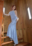 young woman in blue evening gown walking up spiral staircase Stock Images