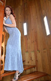 young woman in blue evening gown walking up spiral staircase Royalty Free Stock Photo