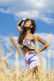 Sexy young woman in blue shorts in a wheat golden field Royalty Free Stock Photo