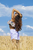 Sexy young woman in blue shorts in a wheat golden field Stock Photography