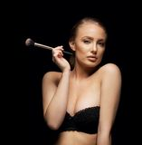 Sexy young woman in bra with a make up brush Stock Image