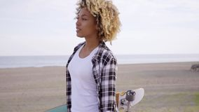 Sexy young woman carrying a skateboard at a beach stock footage